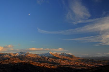 Moel Hebog in Winter late afternoon looking towards the Moelwyns, fingers of cloud lick the moon