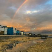 Rainbow over beach huts