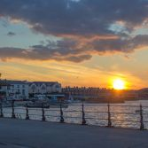 The setting sun over seafront of Swanage.